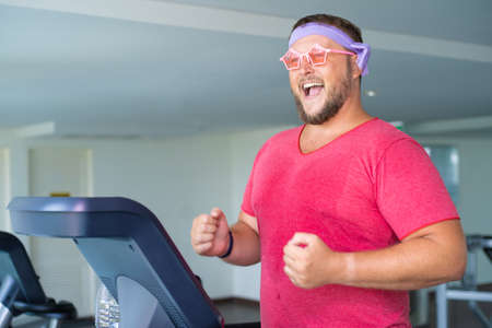 Playful fat man in a pink T-shirt and pink glasses is engaged in fitness in the gym. Archivio Fotografico
