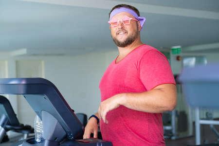 L'uomo grasso allegro in una maglietta rosa e occhiali rosa è impegnato nel fitness in palestra.