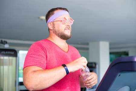 Playful fat man in a pink T-shirt and pink glasses is engaged in fitness in the gym. man drinking water in the gym