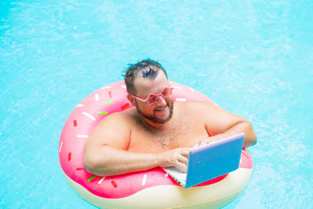 enjoying Funny fat male in pink glasses on an inflatable circle in the pool works on a laptop portraying a girl.