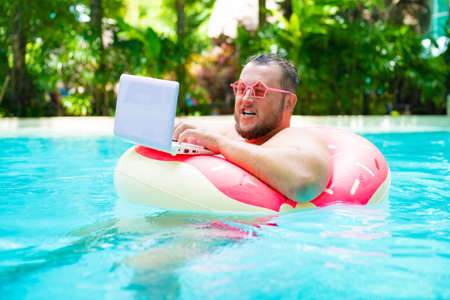 surprised Funny fat male in pink glasses on an inflatable circle in the pool works on a laptop portraying a girl. Imagens