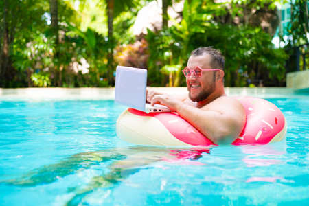 Funny fat male in pink glasses on an inflatable circle in the pool works on a laptop portraying a girl.