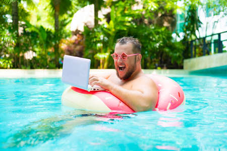 screaming Funny fat male in pink glasses on an inflatable circle in the pool works on a laptop portraying a girl.
