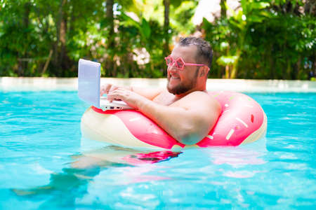 smiling Funny fat male in pink glasses on an inflatable circle in the pool works on a laptop portraying a girl.
