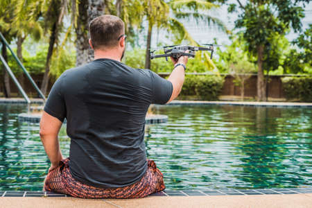 a man launches a drone for flight, with which you can take photos and video filming Stock Photo