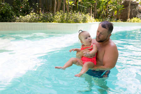 happy father swims in the pool with his daughter
