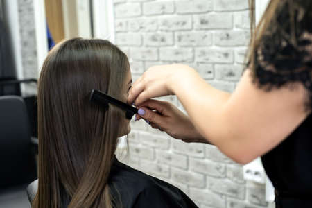 hairdresser makes hair lamination in a beauty salon for a girl with brunette hair