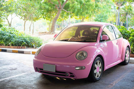 Modern fun pink small car. Photo of a modern funky pink car parked