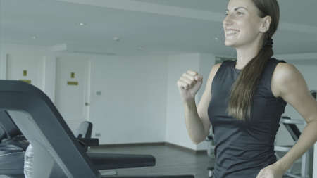 Beautiful fitness girl running and drinking water on treadmill at the gym Stockfoto