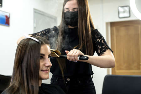 hairdresser makes hair lamination in a beauty salon for a girl with brunette hair Imagens
