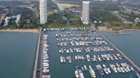 Aerial View by Drone of Yacht Club and Marina. Top view of yacht club. White boats in sea water. Marina dock yachts and small moto. Yacht and sailboat 版權商用圖片