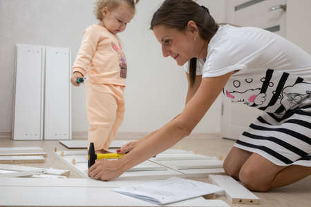 Attractive girl with a little daughter collect furniture with their own hands. The concept of feminism. Stockfoto