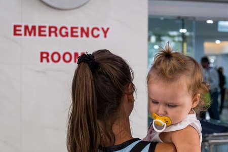 Mamá e hijo entran a la sala de emergencias en la sala de emergencias del hospital. Foto de archivo