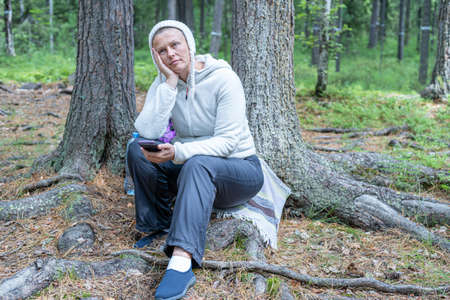 A pretty girl in light clothes, a European-looking ecotourist, sits near a tree in the forest and looks at the phone.