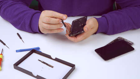 The smartphone repairman repairs the phone, using a screwdriver, unscrews the bolt to replace the smartphone screen. Close up