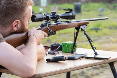 A man with a beard looks into the scope of a sniper rifle, prepares to shoot Standard-Bild