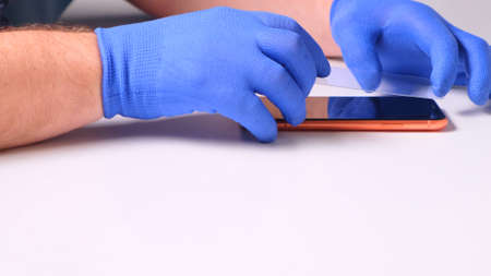 man replaces a broken tempered glass screen protector for a smartphone.