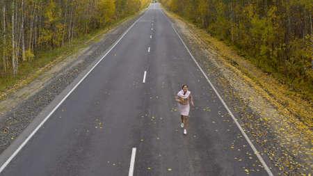 A female walks and runs along an asphalt road through an autumn forest, top view.