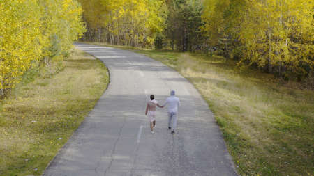 Female and male walks and runs along an asphalt road through the autumn forest, top view.