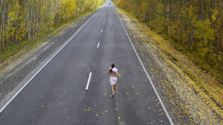 female walks and runs along an asphalt road through an autumn forest, top view.