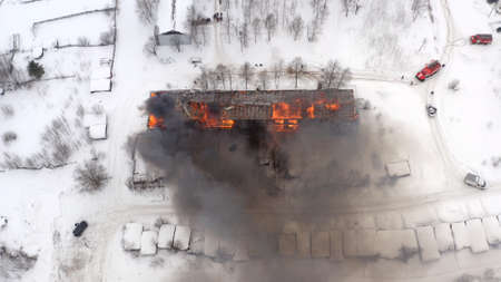 Aerial view the burning roof of the building in winter.