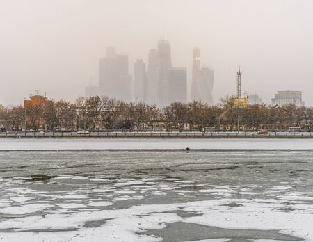 Barely visible complex of buildings with the Moscow City Moskva River embankment in heavy snow