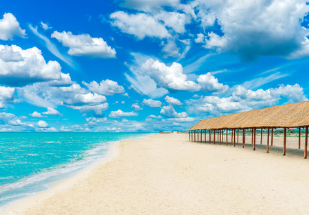 Beautiful tropical sandy beach with canopies from the sun and blue cloudy sky