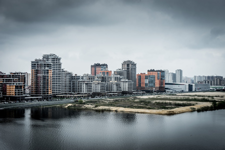 Modern residential buildings on the banks of the river Kazanka. Urban High Contrast Desaturated Look. Cross processed photo Stock Photo