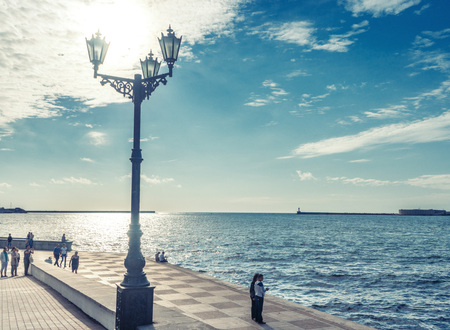 Lantern on the Embankment in Sevastopol. People stand and look at the bay. Photo in vintage style Stock Photo