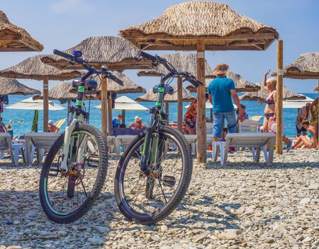 There are bicycles on the sunny beach of the sea.