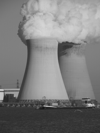 A monochrome photograph of two cooling towers of a nuclear power plant with a passing boat in the foreground.