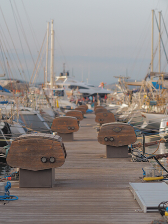 A quay where multiple boats are docked. The boats in the background are out of focus, which gives a dreamy effect.