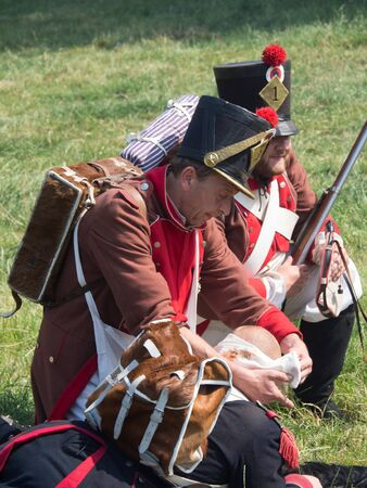 Waterloo, Belgium - June 18 2017: Medics help a wounded soldier at the re-enactment of the battle of Waterloo. 에디토리얼