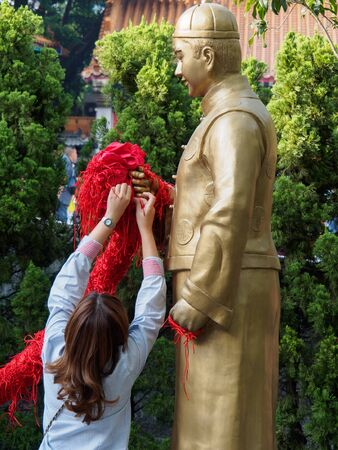 Kowloon, Hong Kong - November 03, 2017: A woman knots a red rope to the statue of Yue Lao at the Wong Tai Sin temple in Hong Kong in the hope of prosperity in love.