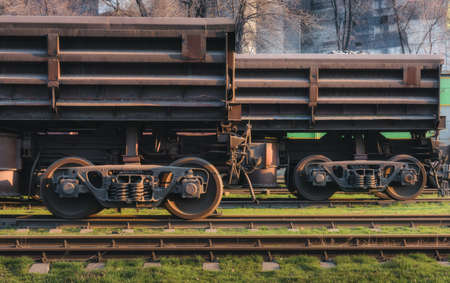 Freight wagons on the railway station and train against metallurgical plant at sunset. Industrial view. Close-up. Railroad in the evening. Railway platform. Heavy industry. Cargo shipping