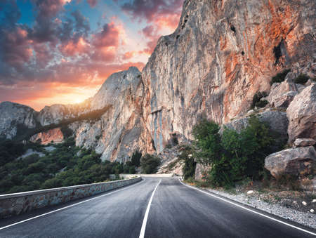 Beautiful asphalt road. Colorful landscape with high rocks, mountain road with a perfect asphalt, trees and amazing sunny cloudy sky at sunset in summer. Travel background. Highway at mountains. Road Stock Photo