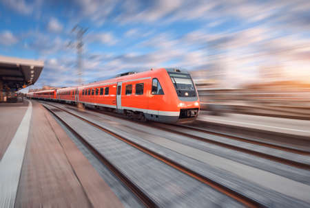 Red modern high speed train in motion on railroad track at sunset in Europe. Train on railway station with motion blur effect. Industrial landscape with train, railway platform and colorful sky Stock Photo