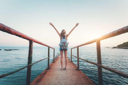 Paisaje de verano con mujer joven de pie en el muelle de mar viejo con los brazos levantados al atardecer. Tono de la vendimia. Chica en la orilla del mar, agua turquesa y cielo soleado en la noche. Estilo de vida Foto de archivo