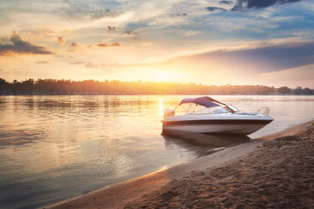 Colorful sunset with boat ot the river bank. Summer landscape with pleasure boat, river, bright sky with clouds and yellow sunlight reflected in water, trees and beach. Amazing view on the lake