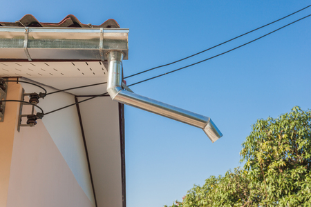 on a roof hangs a drainpipe next to a tree
