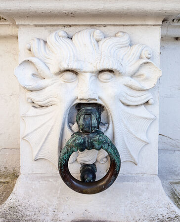 to a pillar is a stone lion with an iron ring in its mouth photo
