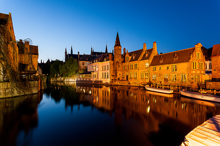 In Brugges at sunset during the blue hour, you see the refection of the building and the tower