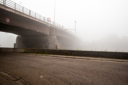 this bridge is under a thick fog the morning of the day photo