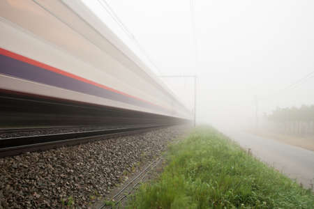 hangs a thick fog along the road and rail photo