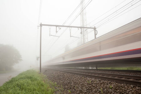 hangs a thick fog along the road and railway passing a train photo