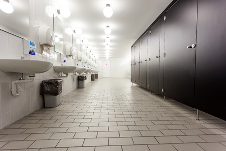 Mens restroom in an public building in white and black doors Stockfoto