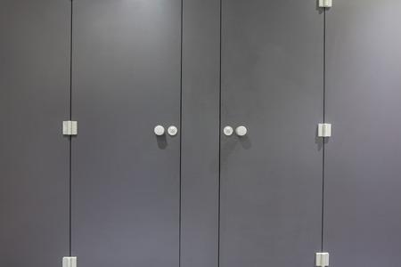 Mens restroom in an public building in gray doors