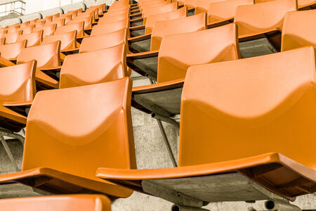 orange chairs: row of orange plastic chairs that disappear into the distance Stock Photo