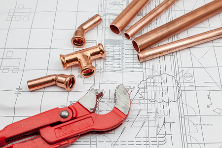 architect tools: Plumbing Tools Arranged On House Plans whit copper tubes