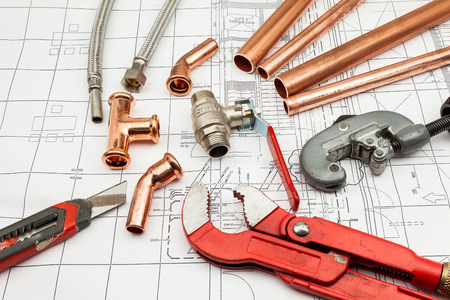 Plumbing Tools Arranged On House Plans whit copper tubes